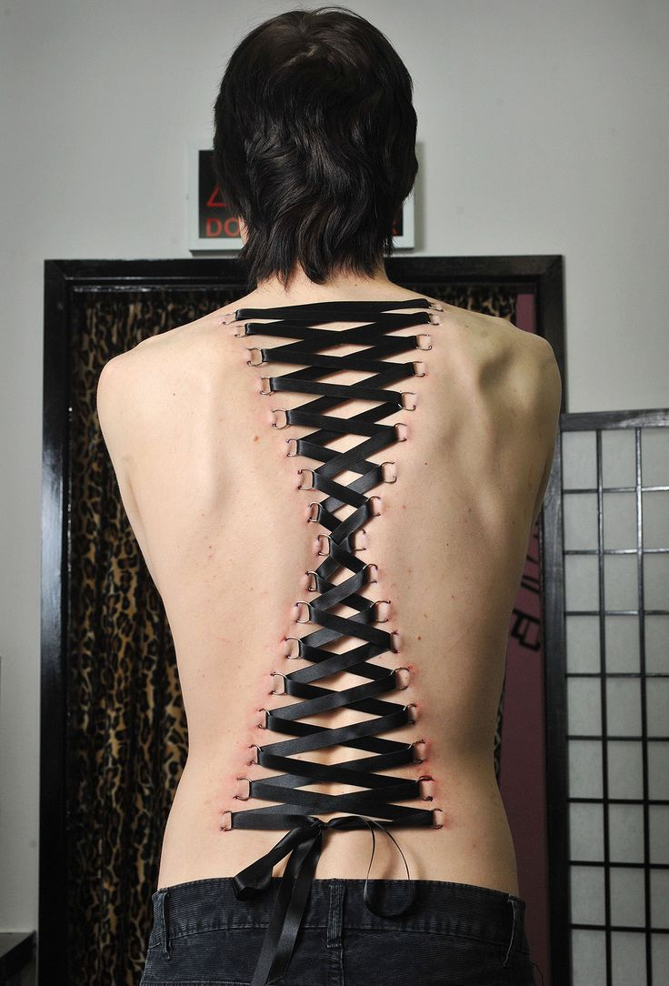 Woman shows off bizarre zigzagging ribbon trend known as corset piercing