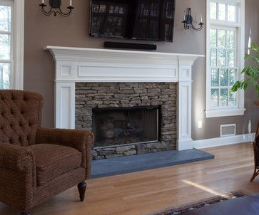 Fireplace mantel in white with stacked stone surround set a top volcanic stone a traditional-family-room. http://www.kmrenovate.com