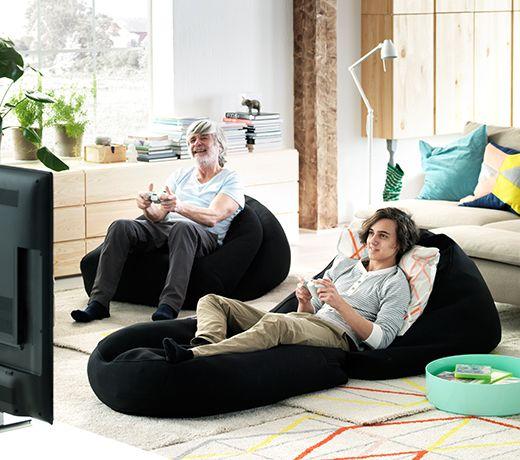 Grand-père et petit-fils assis sur des fauteuils poires IKEA et jouant à un jeu vidéo ensemble.