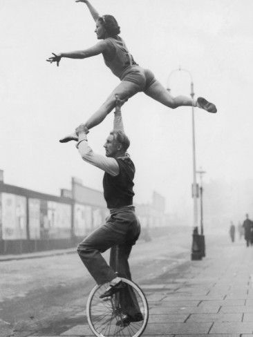 Male Acrobat on Unicycle Supporting Woman in Air Photographic Print at AllPosters.com