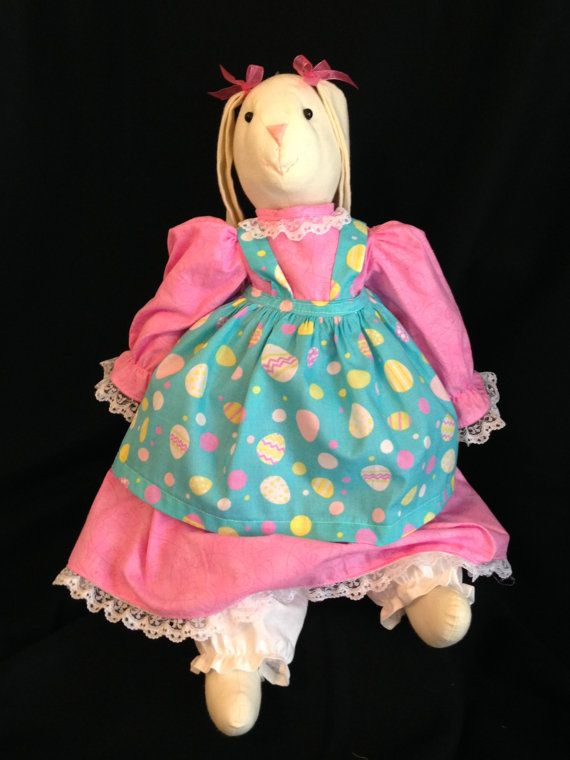 """Handmade Muslin Bunny made with Natural Muslin, 2 Button eyes, A Bright Pink Swirl Dress, Turquoise Egg Easter Fabric for the Apron and White Muslin for the Bloomers. They are approx. 20"""" Tall. These can be used for either decorations or for gift giving. Not Recommended to be given to children under the age of 3 because of the button eyes. I have them sewn securely but its never good to take the chance with the little ones. I have several different colors available and will be including non…"""