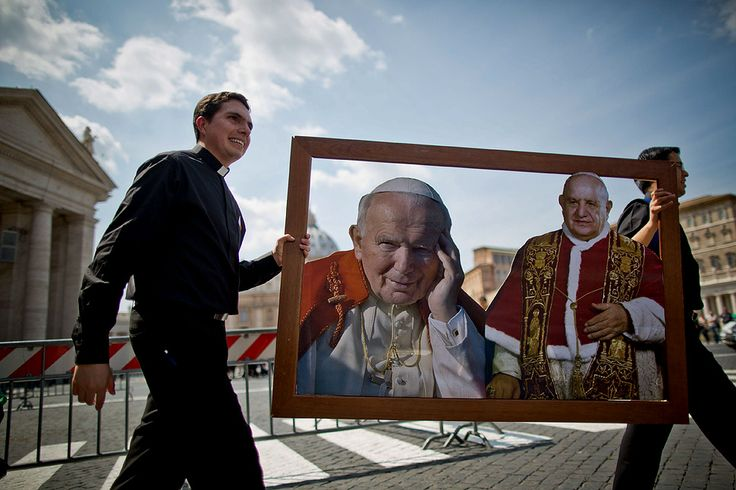 Seminarians from the Legionaries of Christ religious order hold a picture depicting former popes John Paul II, left, and john XXIII near St. Peter's square in the Vatican. People are arriving for the historic double canonization of both former pontiffs, which is expected to draw around 1 million pilgrims and tourists.