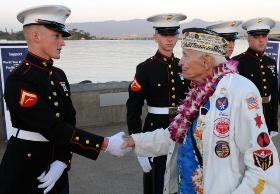 Pearl Harbor survivor Allen Bodenlos, right, shakes hands with a member of a U.S. Marine Corps ceremonial rifle team, left, before the start of the commemoration of the 69th anniversary of the attack on Pearl Harbor at the Pearl Harbor Visitor Center at the World War II Valor in the Pacific National Monument