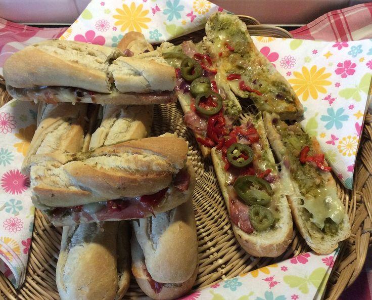 Lekker stokbroodje met pesto, Serrano ham, gebakken uien en paprika, mozzarella en jalapenopepers. Hou je niet van pittig, dan laat je de pepers weg.