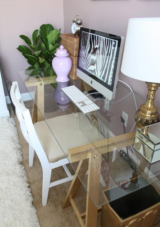 desk- $5 ikea sawhorses painted gold with piece of glass on top
