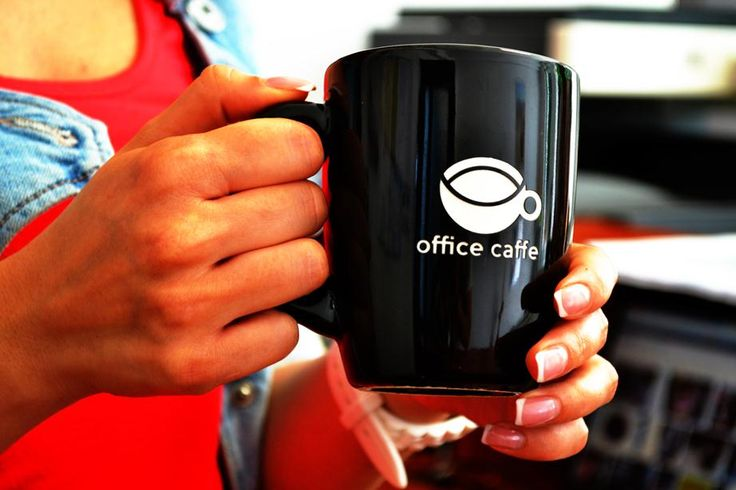 Girl's hands, with officecaffe coffee cup in the office. Copyright © OfficeCaffe 2013. All rights reserved