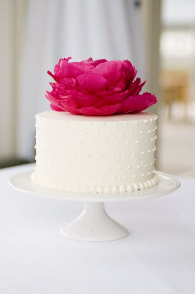 wedding cake with simple white dots and one over-sized bloom