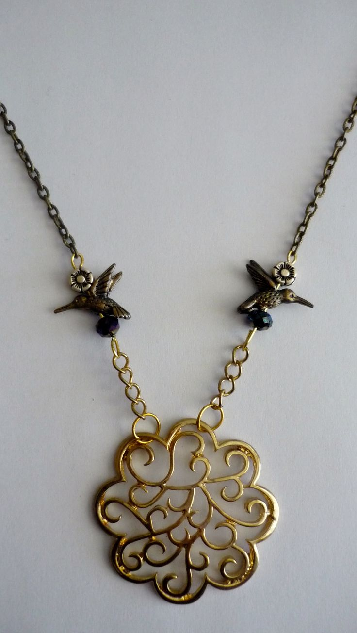 Amanda Harris Gold filagree pendent on gold/silver/bronze chain with gold hummingbirds and bead/flower charms.