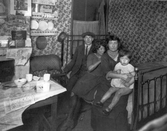 A family huddle together in a slum tenement, Lisburn Street, Bethnal Green, 1923
