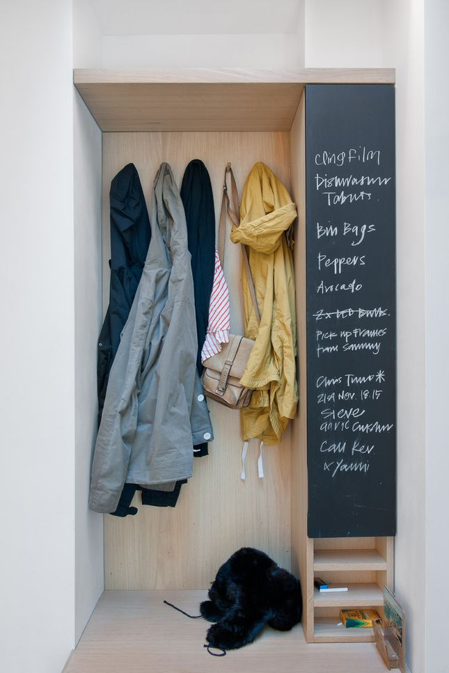 A built-in closet and chalkboard surface in the entry keeps things tidy and the couple's to-do list in order. Photo by: Andrew Meredith | Read more: http://www.dwell.com/articles/Collectors-Choice.html