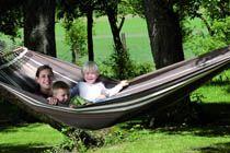 PARADISO SILVER HÄNGMATTA  Paradiso är en typisk brasiliansk familje-hängmatta som är vävd av extra tjockt bomullstyg. De extra tjocka snörena på ändarna sätts fast för hand med ett vävt band så att hängmattans ändar blir starkare och därmed håller extra länge.  Den är hela 175 cm bred så här finns det gott om plats för familjemedlemmarna eller den som vill ha extra utrymme åt sig själv. Vi brukar säga att ju större hängmatta desto skönare är den.