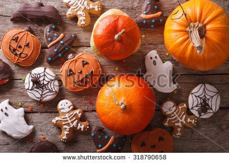 Beautiful gingerbread for Halloween and fresh pumpkin on the table. horizontal…