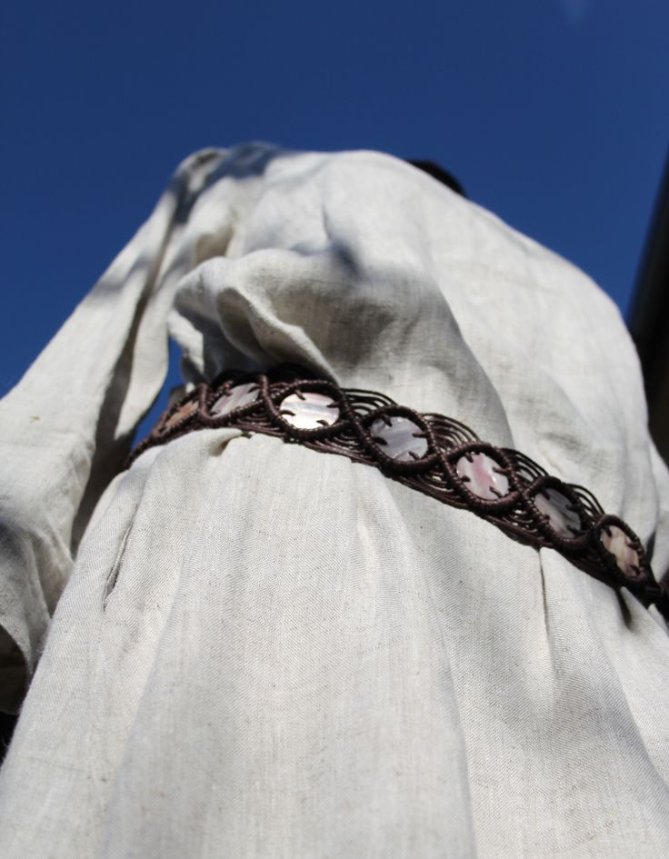 Linen natural dress, clothing. Dlouhé lněné šaty jednoduchého áčkového střihu s dlouhými rukávy a dvěma kapsami v bočních švech. Zcela jednoduché, s minimem švů, vhodné ke kombinování s dalšími zajímavými, například barevnými kousky oblečení nebo s výraznými šperky (kostěnými, dřevěnými apod.), pásky nebo s kůží.