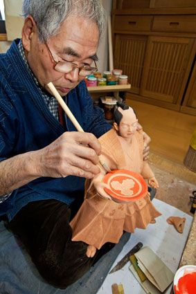 Craftsman at work making a Hakata doll.