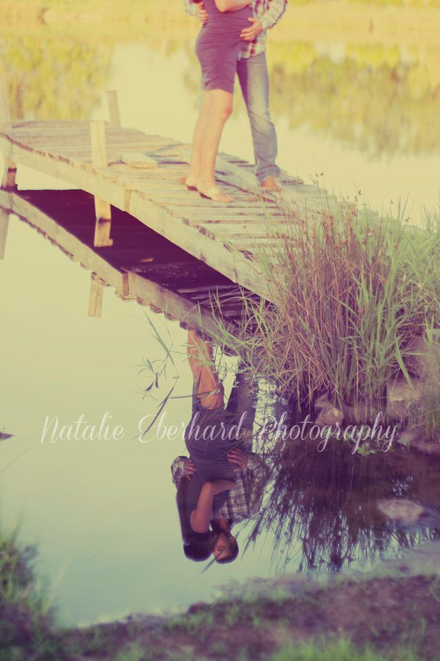 Maternity couple reflection pose on pond dock. Romantic country scene. Photo by Natalie Eberhard Photography, Nevada, MO