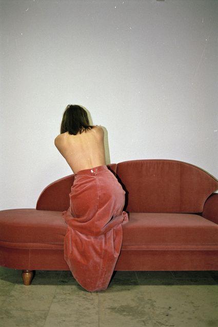 Perfekt kalkulert i forhold til sofaen. Det er nok meningen. Naken rygg. Naken vegg. Rødoransje fløyel.