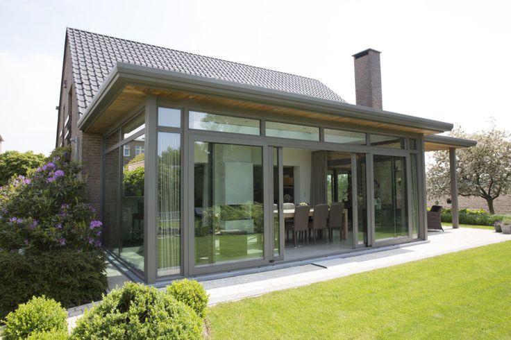 Leefveranda op maat door Verandaland Perfecta uit Herentals. Moderne veranda met als uitbreiding een pergola (op deze manier ontstaat er een overdekt terras). De veranda heeft een grote schuifdeur aan de voorzijde om de link met de tuin extra in de verf te zetten.