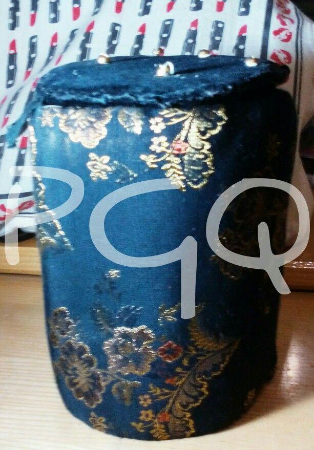 Caja cilíndrica hecha con cartones acolchada y forrada con telas.