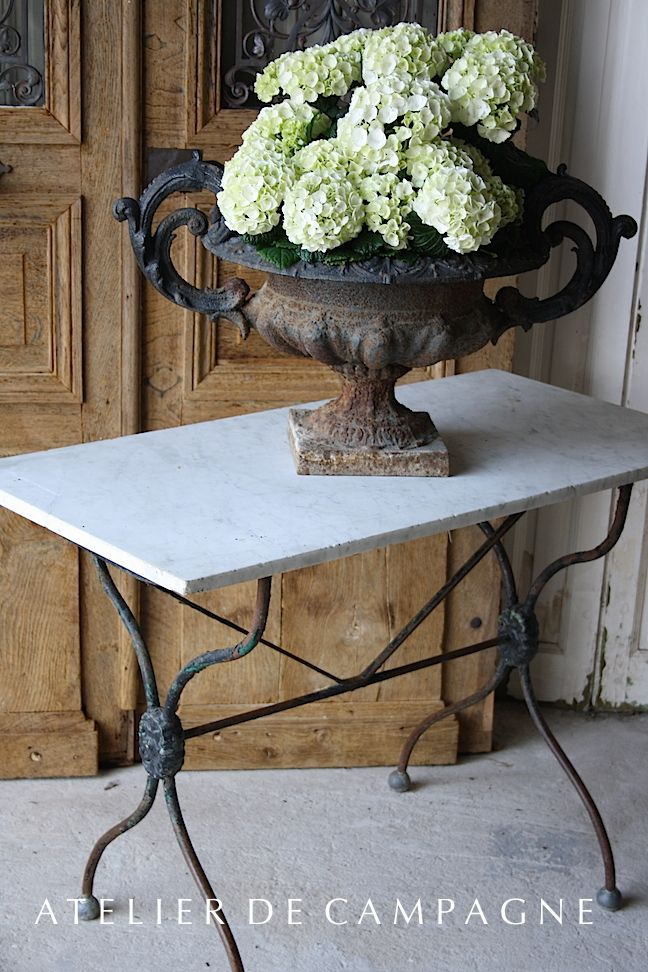 Antique wood doors, marble top table, bowl of hydrangeas make a great vintage rustic statement in an entry!