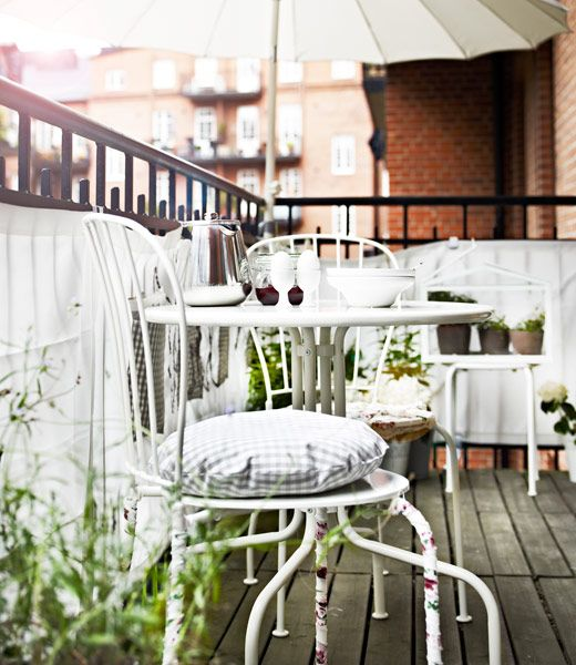Plants, fabric, table and chairs dress the balcony.  LÄCKÖ outdoor furniture.