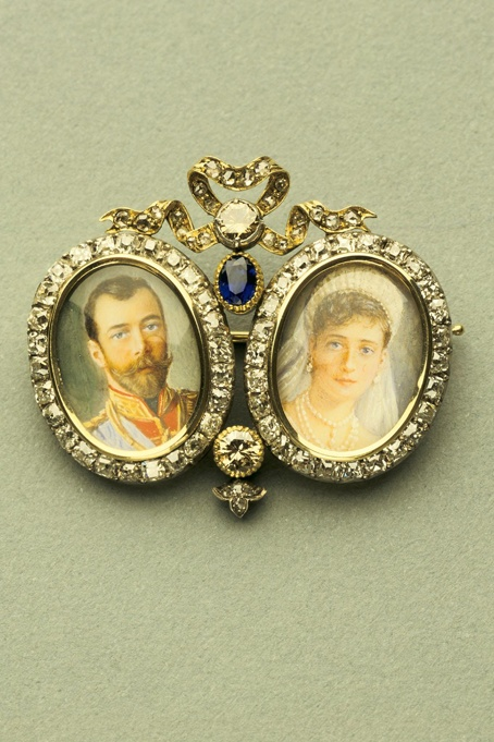 Brooch with Miniatures of Nicholas II and Alexandra  Fabergé (firm); Perkhin, Mikhail (workmaster)  RUSSIA: Saint Petersburg  Ca. 1896  Gold, diamonds, sapphire, miniatures  H. 1 3/8 in., W. 1 9/16 in.