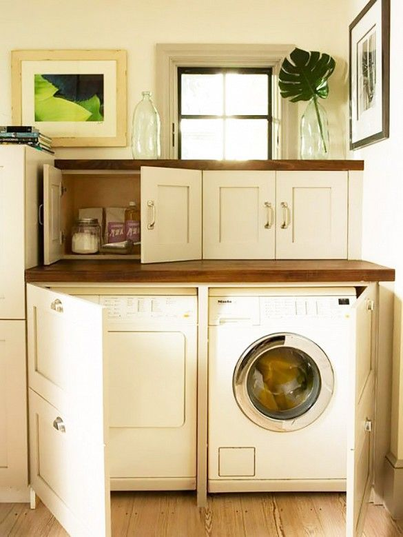 Laundry appliances are hidden behind white cabinet doors with wooden counter tops