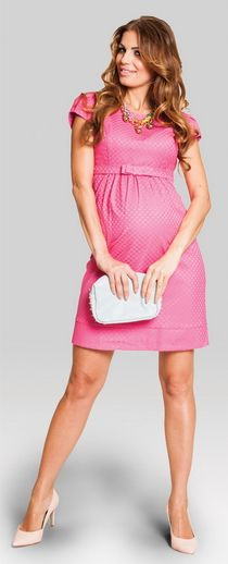 Pinkly smiling lightly tanned chocolette in pink cap-sleeve mini maternity dress w/ subtle scalework pattern & matching narrow belt, nude kittens clutching white clutch