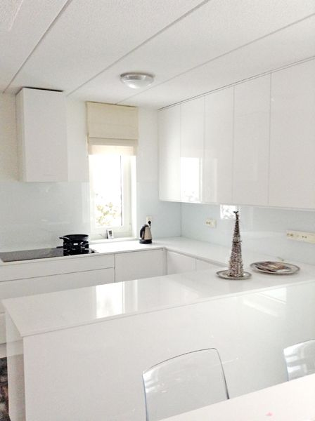 Kaapistoissa valkoiset korkeakiiltolakatut ovet, tasoina valkoiset kvartsitasot ja välitilassa valkoinen lasi.