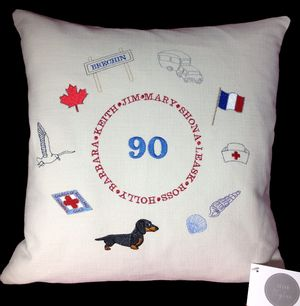 LIFETIME STORY CUSHION A ninetieth birthday celebration cushion embroidered with mementoes of special significance to the lady.