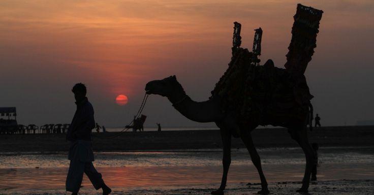 20151231 - Um paquistanês e seu camelo se destacam em bela paisagem do último fim de tarde do ano, em Karachi, no Paquistão. PICTURE: Fareed Khan/AP