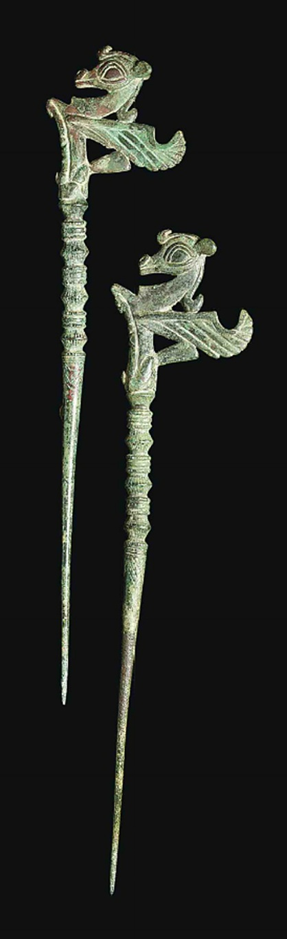 TWO LURISTAN BRONZE PINS   CIRCA EARLY 1ST MILLENNIUM B.C.   With terminals in the form of stylised winged bulls, the knopped and ridged shafts with incised decoration  10 1/8 in. (25.7 cm.) long max.