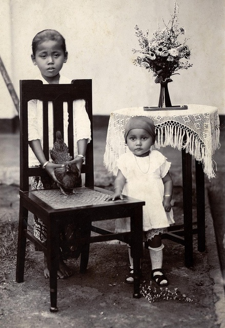 Willy Klaauwer (1924), daughter of a Dutch KNIL soldier and a woman from Java, posing with her aunt Jet Kasanpawiro who is holding Willy's favourite chicken. Western Java, Dutch Indies (Indonesia), 1926.