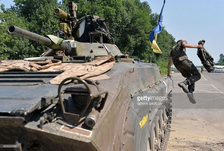 A Ukrainian serviceman jumps off an armoured personnel carrier (APC) at a checkpoint near the eastern Ukrainian city of Debaltseve in the Lugansk region on August 1, 2014. Dutch and Australian experts finally got to work at the crash site of downed flight MH17 in eastern Ukraine, after fighting between government troops and pro-Russian rebels killed at least 14 people.