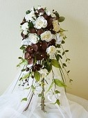 NATASHA - Moder, natural looking, cascading shower bouquet featuring ivory open roses with chocolate brown phalaenopsis orchids and ivory gloriosa lilies.