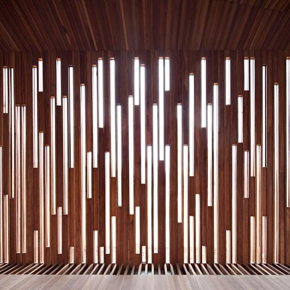 This Patterned Wood Wall is an amazing feature! The combination of the dark red wood panels with the bright white lights looks great! The use of having vertical lines help increase the appearance of height in the room, which is an added bonus! I love how the paneling blends straight into the ceiling and the floor!: