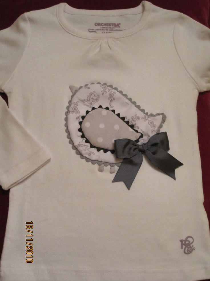 Camiseta Blanca con dibujo de pajarito en dos telas en tonos grises. El lazo va unido a la camiseta a través de un corchete para que pueda...