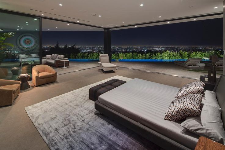 Opening to a spacious terrace and 65-foot infinity pool, this sleek bedroom boasts all the comforts of the indoors with incredible outdoor amenities.