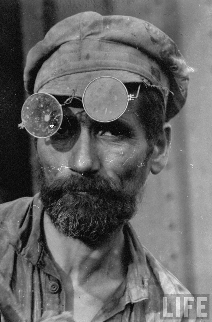 """Closeup portrait of Russian iron puddler, with dark glasses parked over his brow at the """"Red October"""" Rolling Mills, Stalingrad, 1931 by Margaret Bourke-White"""