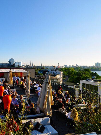 """In der Hamburger Hotelbar """"Campari Lounge"""" hält man es """"very british"""": schwere Möbel, gedämpftes Licht, fantastischer Whisky. Durchkreutzt wird dieses Ambiente vom Alsterblick der Dachterrasse. Eine so spektakuläre Aussicht auf Hamburgs Alster findet man kein zweites Mal."""