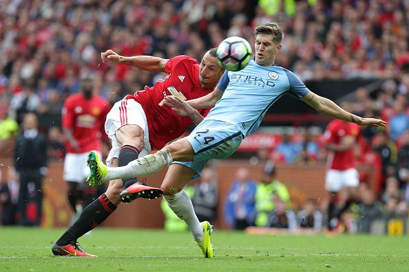 Zlatan Ibrahimovic of Manchester United competes with John Stones of Manchester…