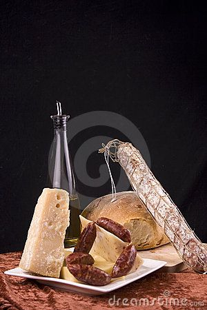 An assortment of Italian breads, cheeses, wine and salami.