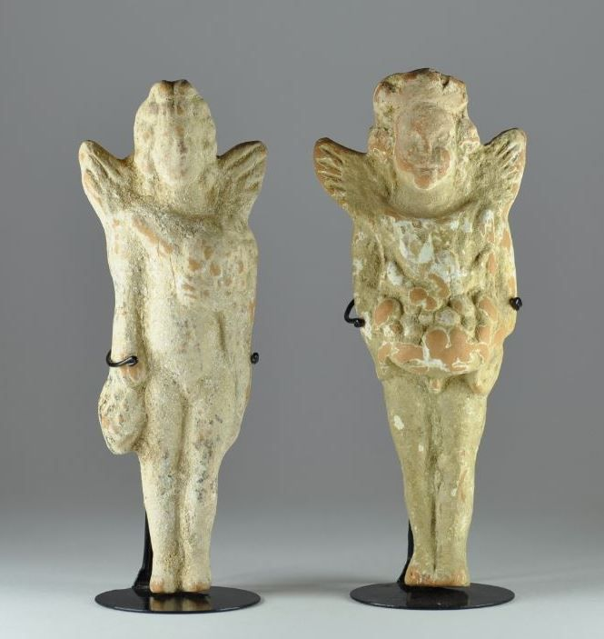 Greek Eros statuettes, hellenistic period, 2nd century B.C. Greek terracotta winged putti holding one basket of fruit and other a bunches of grapes, 13.9 cm high. Private collection