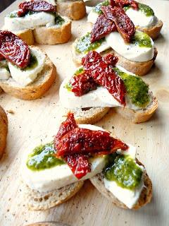 Kleine broodjes met mozarella, pesto en gedroogde tomaten.