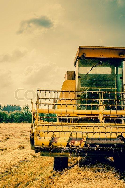 Stock image of 'Close-up photo of a yellow harvester machine'