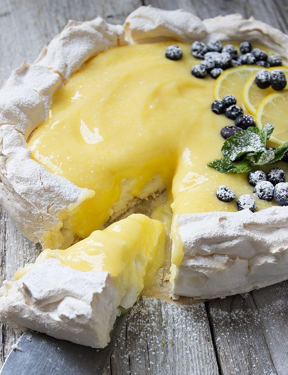 A delicious, light and fresh dessert, with a meringue base and a light lemon curd topping. Garnished with fresh lemon slices, blueberries, mint leaves and powdered sugar.