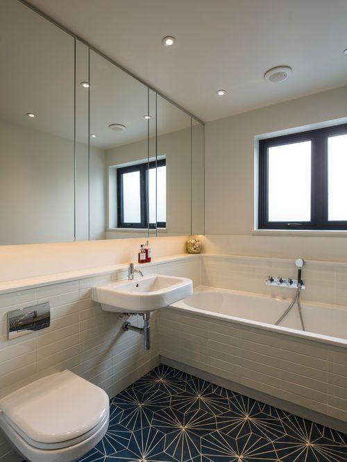 Cette image montre une salle de bain nordique avec un plan de toilette en quartz modifié, un carrelage blanc, un WC suspendu, un lavabo suspendu et un mur blanc.