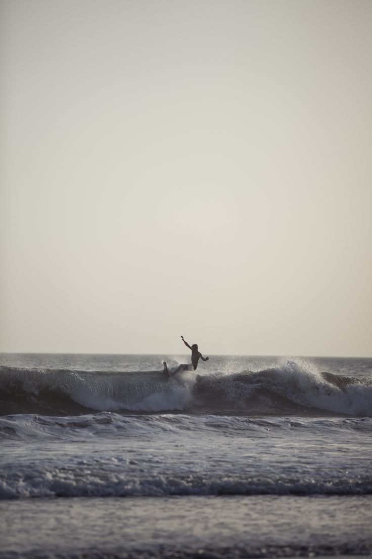 A surfer enjoying the last bit of this wave in Nicaragua.