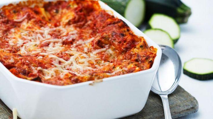 (4 porsjoner) ◗ 4 små squash◗ 1 løk◗ 100 g parmesan◗ olivenolje til steking◗ 1 stort beger cottage cheese, 400 ml◗ 1 ts muskat◗ salt◗ nymalt pepper◗ 8 dl ferdig pastasaus◗ 1 pakke, 300 glasagneplater Tilbehør:◗ godt brød 1. Sett ovnen på 220º. 2. Skyll squash og riv dem på den grove siden på rivjernet. Rensk løk og hakk den fint. Riv parmesan.