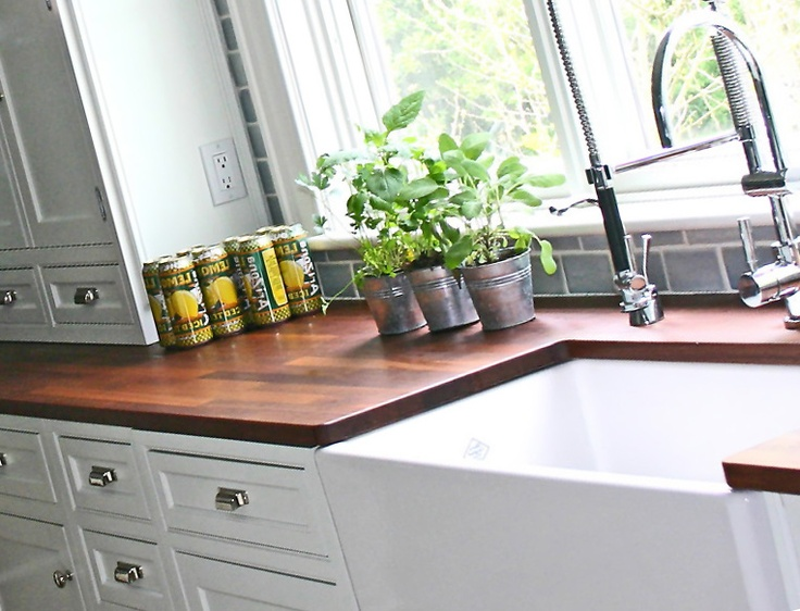 White cabinets with dark Bucher block counter tops and farm style sink <3
