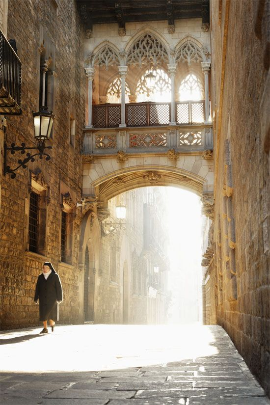 On a cold but sunny spring morning, a nun walks past a Gothic-style arch in Barcelona's Gothic Quarter. Photo ©Mike Randolph.